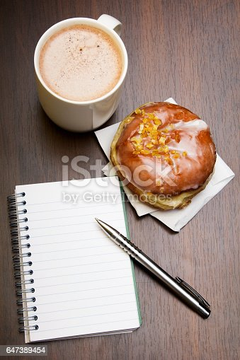 istock Open notebook, donut and cup of coffee on wooden table, 647389454