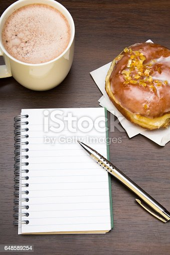 istock Open notebook, donut and cup of coffee on wooden table, 648589254