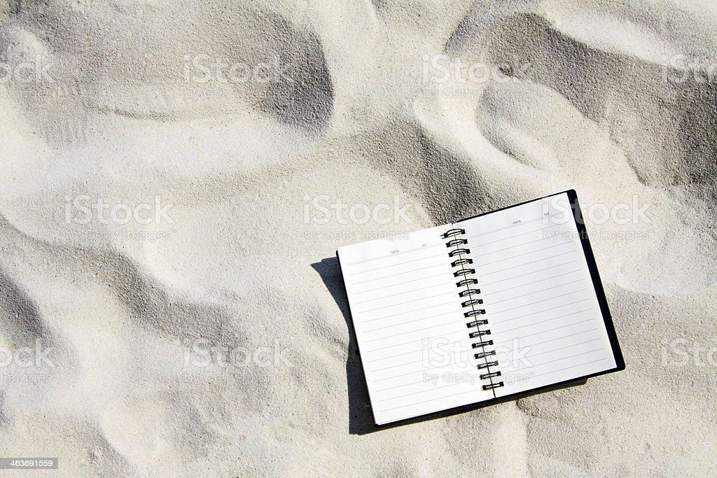 Open notebook on sand beach. stock photo