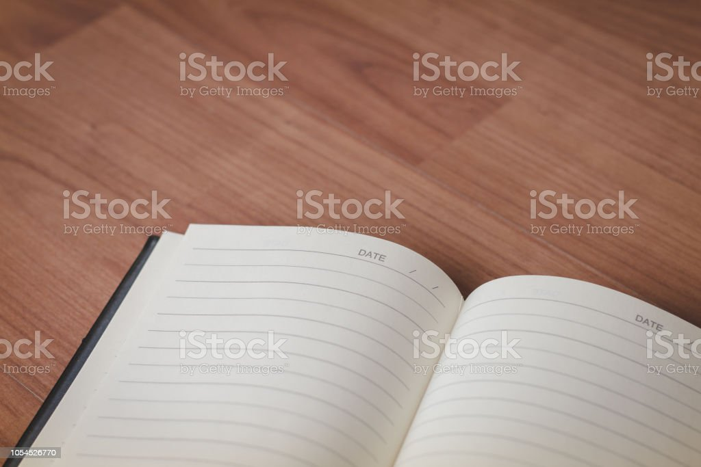 Open notebook on the old wooden floor. stock photo
