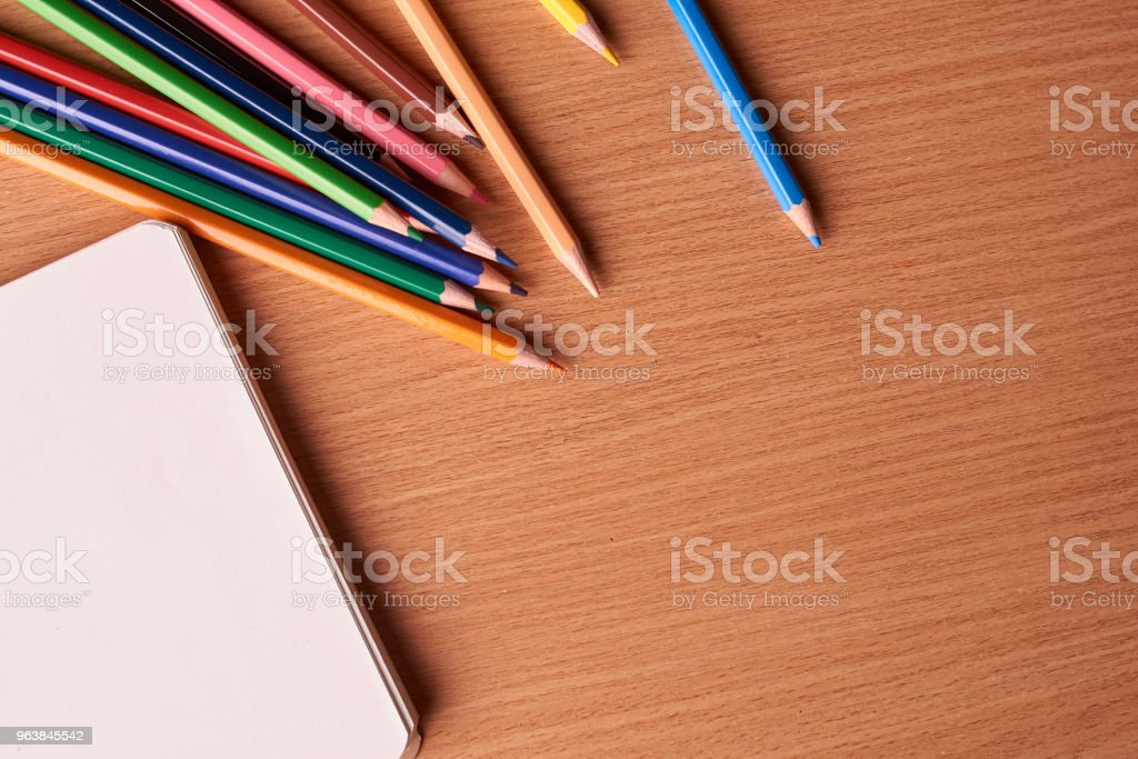 Open notebook on wooden background with colorful pencils and eraser. Flat lay - Royalty-free Above Stock Photo