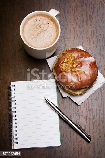 istock Open notebook, tasty donut and cup of coffee on brown wooden table, copy space. 672222954