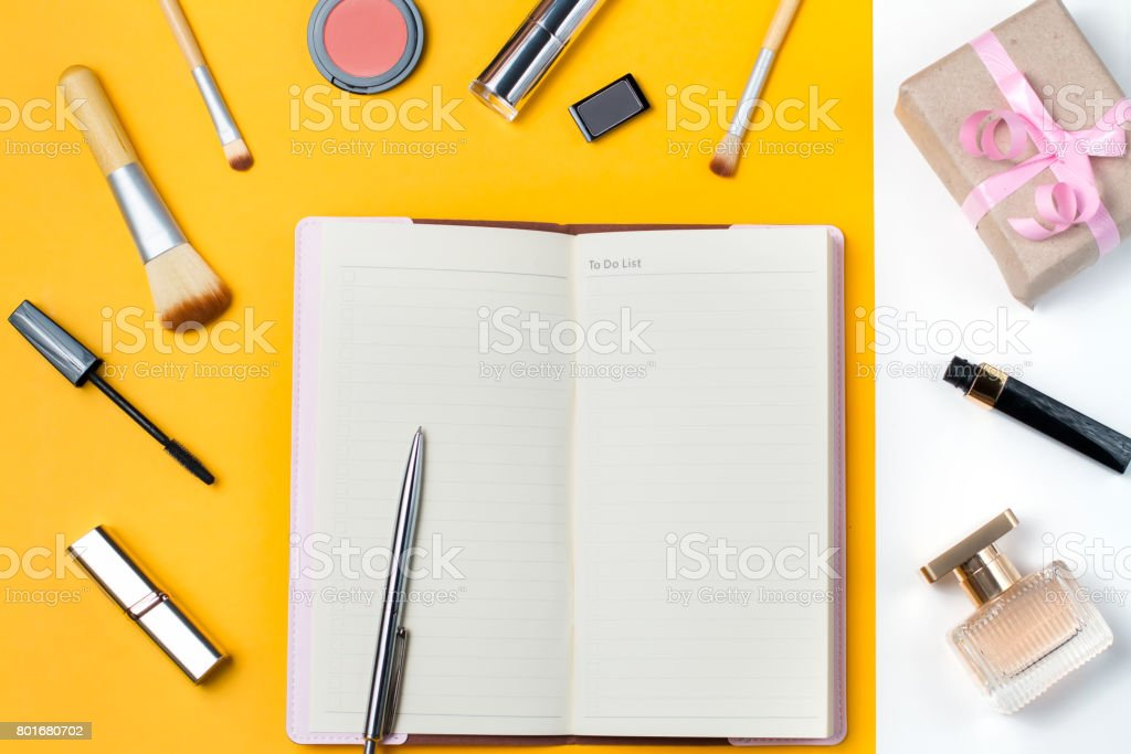 open notebook to do list make up items perfume and gift box on