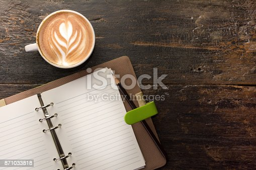 istock Open notebook with a cup of latte coffee on table. 871033818