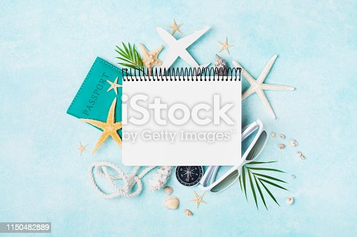 936373320 istock photo Open notebook with accessories on blue pastel table top view. Planning summer holidays, travel and vacation background. Flat lay. 1150482889