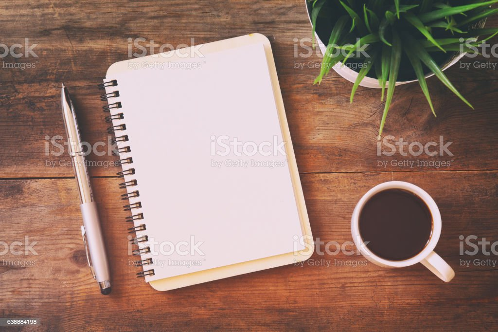 open notebook with blank pages next to cup of coffee stock photo