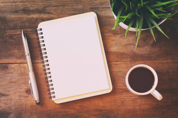open notebook with blank pages next to cup of coffee - foto de acervo