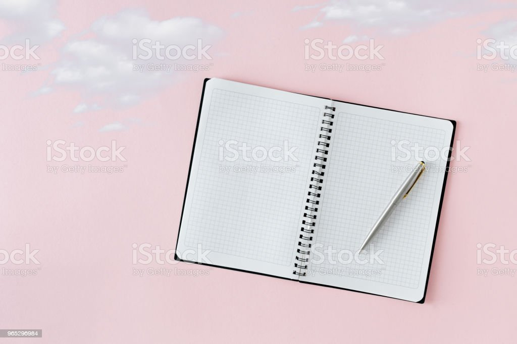 Open notebook with pen on pink background with clouds. Creative minimal dream concept royalty-free stock photo