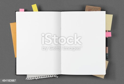 Open notepad with papers, business cards and clipping, post-it
