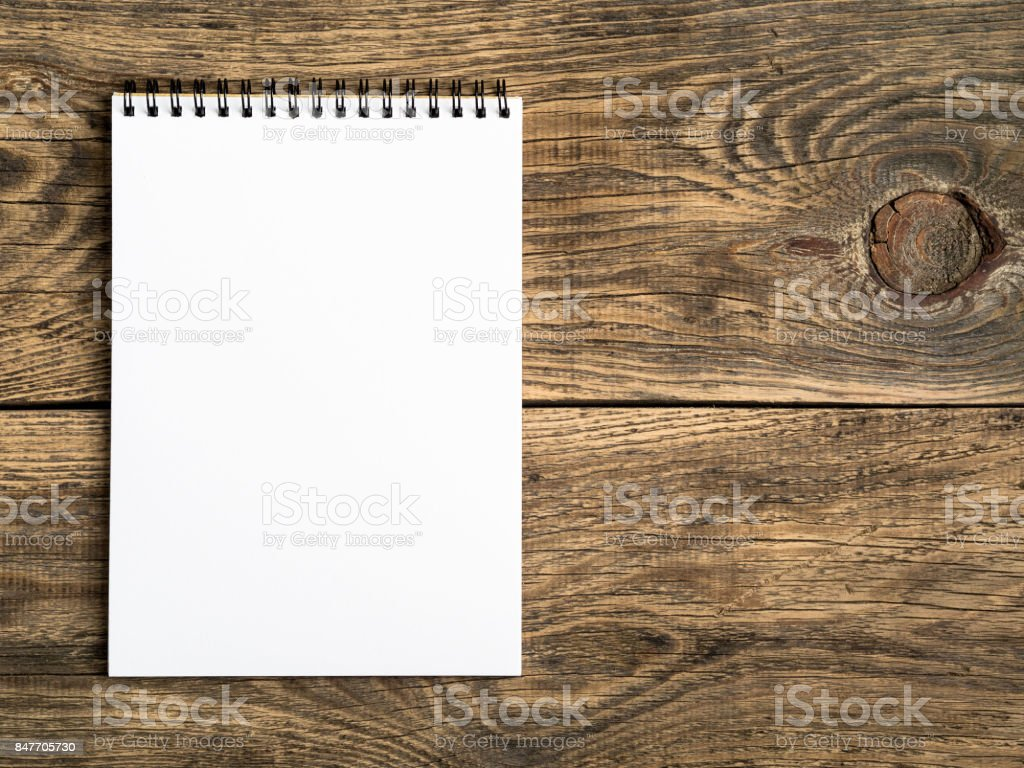 open notepad with a clean white page on wooden table, top view stock photo