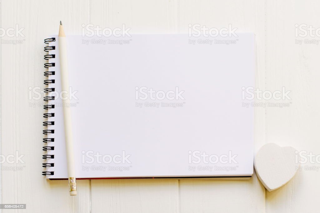 Open notepad with empty page for copy space with a pencil and white wooden heart on wooden milk white background stock photo