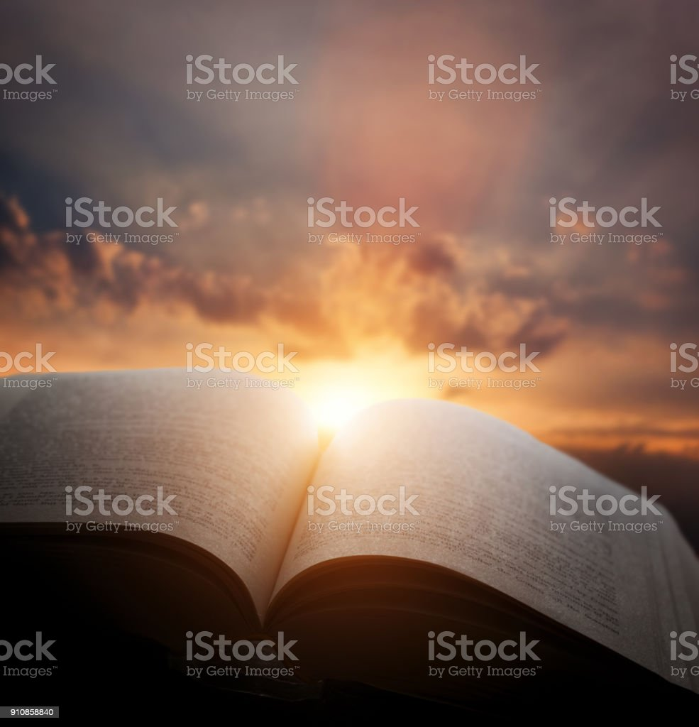Open old book, light from the sunset sky, heaven. Fantasy,...