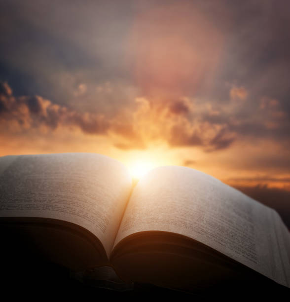 Open old book, light from sunset sky, heaven. Education, religion concept stock photo