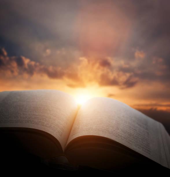 Open oud boek, licht van avondrood, hemel. Onderwijs, religie concept foto