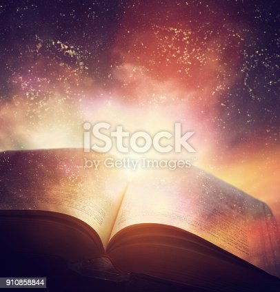 istock Open old book merged with magic galaxy sky, stars. Literature, horoscope 910858844