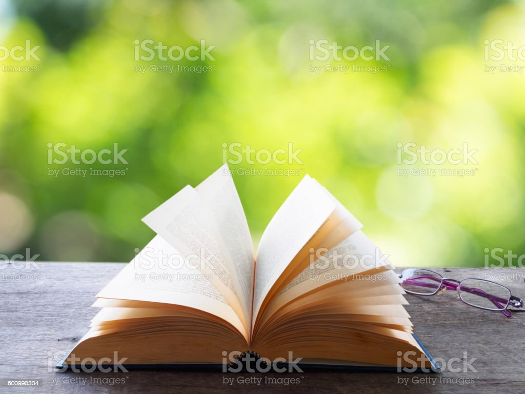 Open old book  with glasses on wooden table in garden - foto de stock