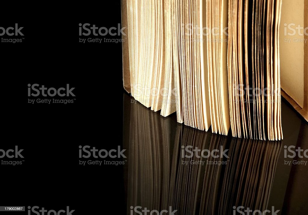 Open old book with vintage pages reflected royalty-free stock photo