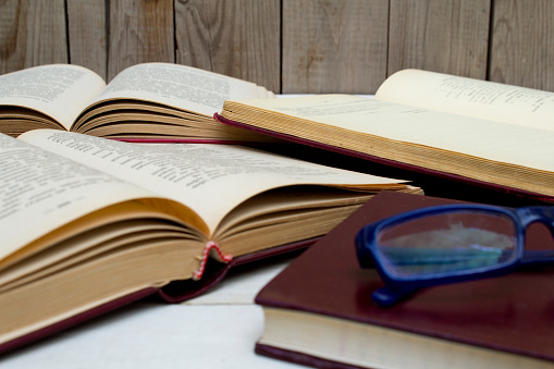 Open old books and glasses on wooden background. Close up.