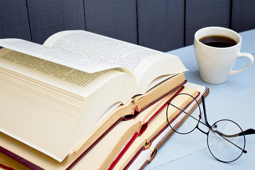 Open old books, glasses and coffee cup on wooden background. Close up.