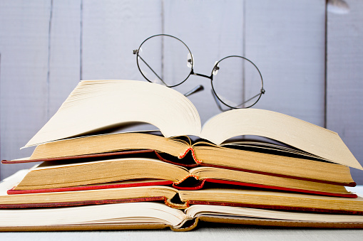 Open old books with glasses on wooden background. Close up.