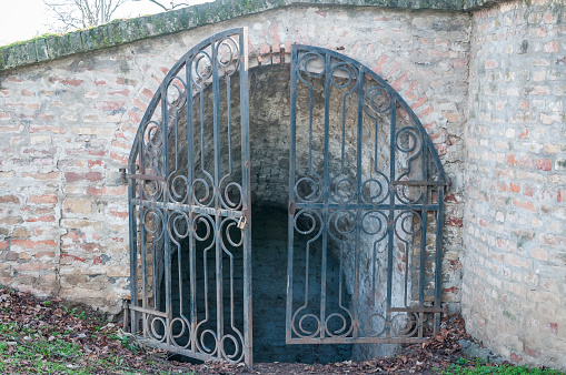 Open old rustic iron gate with padlock on entrance of brick wall underground tunnel