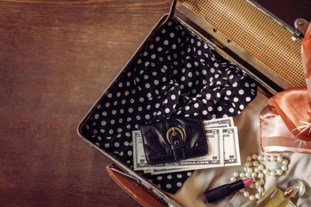 offen alter koffer mit frau kleidung, schmuck, lippenstift, parfüm und us-dollar. historische atmosphäre. braune vintage-stil. retro-dinge-konzept für unterwegs. - geld schön verpacken stock-fotos und bilder