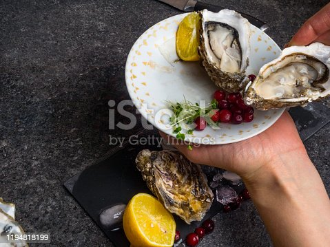 Open oyster in hands, against a background of open oysters, selective focus.