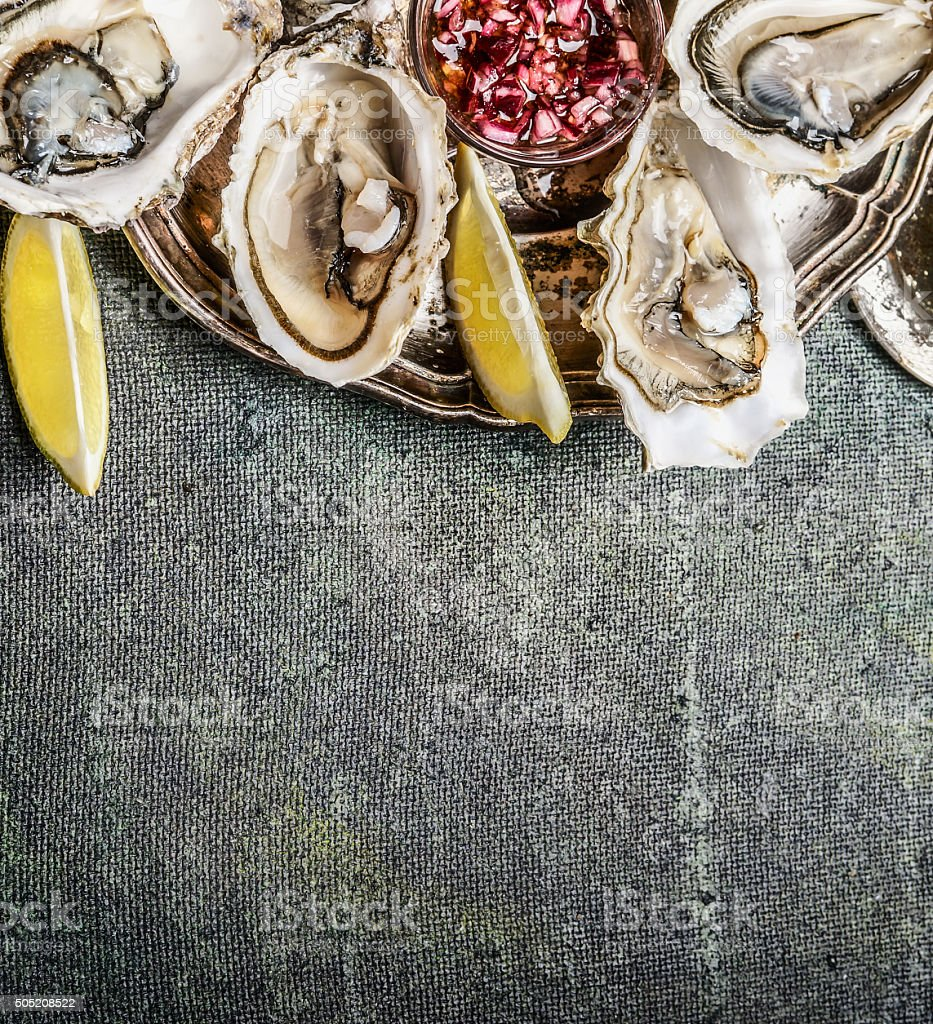 Open Oysters in plate with lemon and shallots sauce stock photo