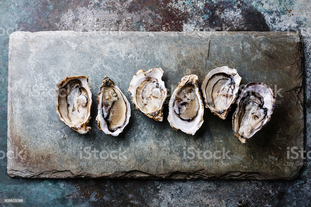 Open Oysters on stone plate stock photo