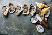 Open Oysters Fines de Claire on stone plate background with lemon and oyster knife