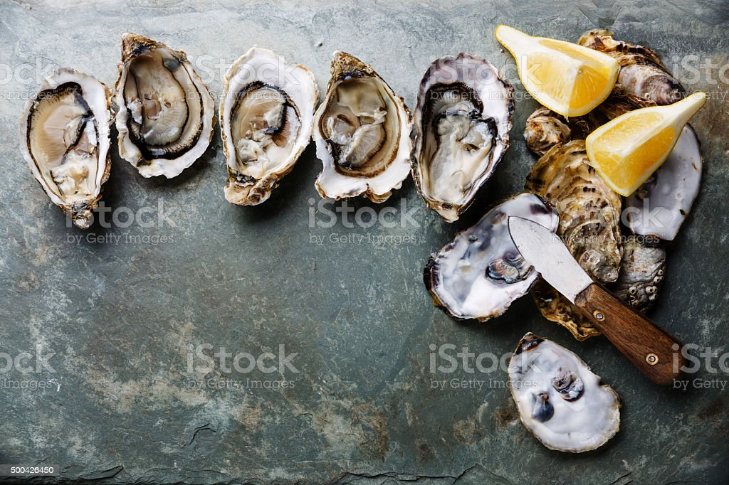 Open Oysters with lemon and knife stock photo
