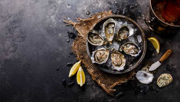 Open Oysters with lemon and Rose Wine in ice bucket stock photo