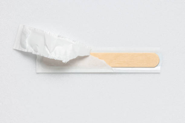 Open packaging with sterile wooden medical spatula stock photo