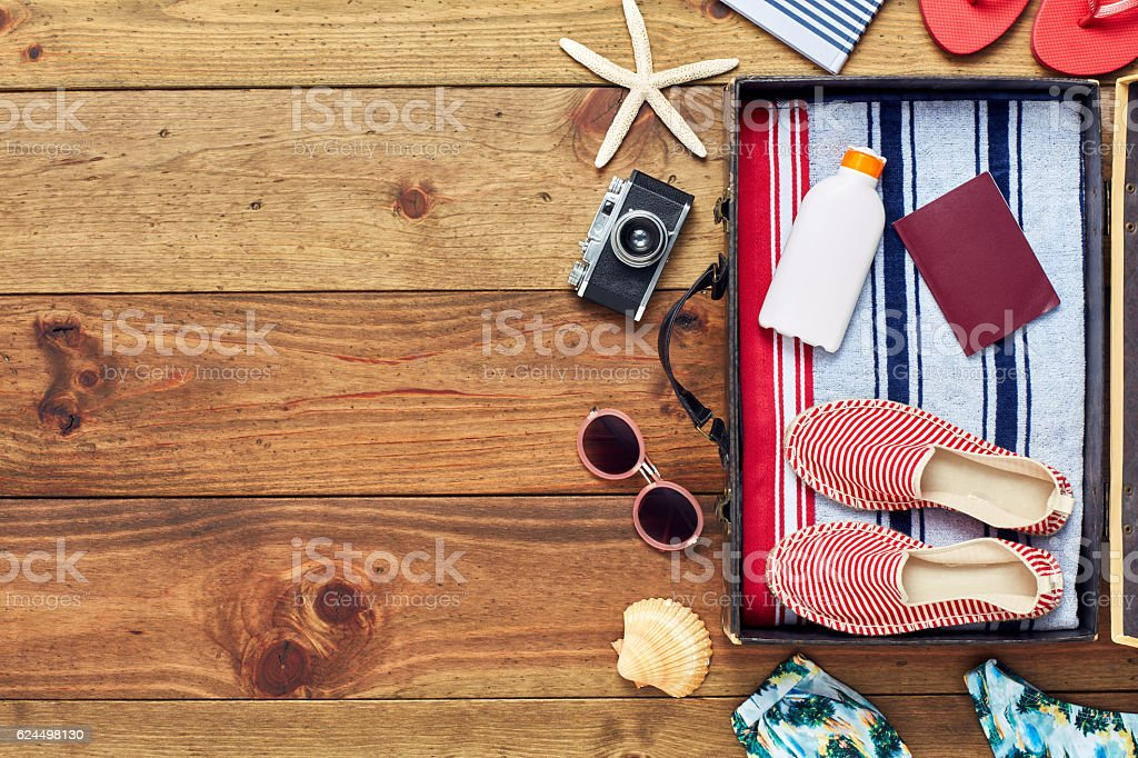 Open packed suitcase with vacation accessories flat lay on floor stok fotoğrafı