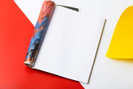 Open page magazine on red and white background, top view.