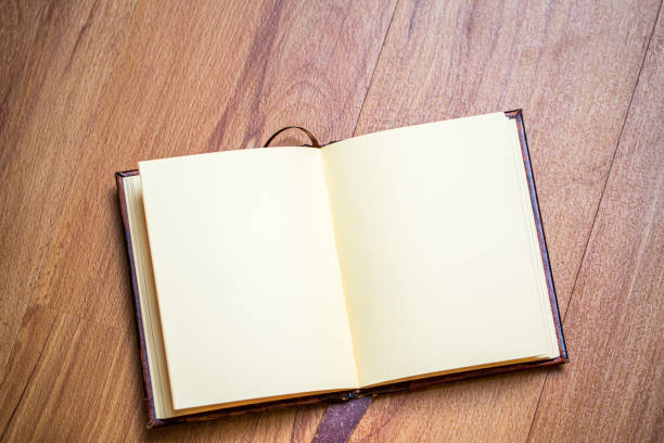 open page notebook on wooden floor. stock photo