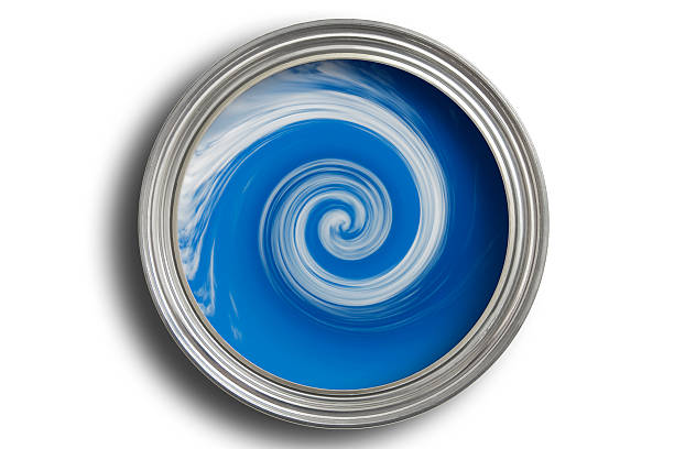Open paint tine with blue paint being mixed in it stock photo