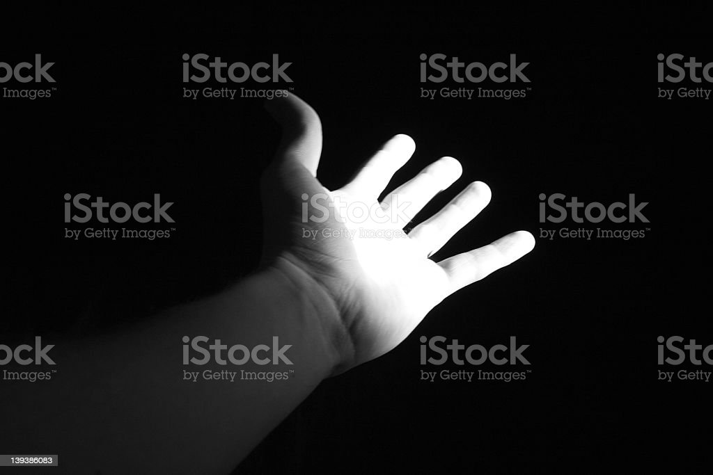 Open palm hand reaching out into darkness stock photo