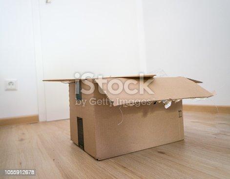 istock Open parcel box on floor torn 1055912678