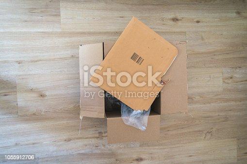 istock Open parcel box on floor torn 1055912706