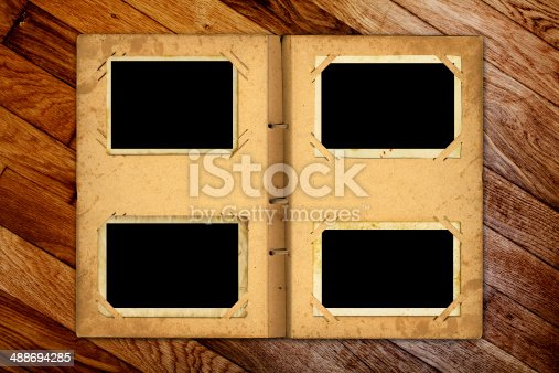istock Open photoalbum with ribbon for photos on the wooden table 488694285