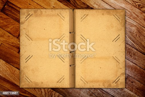 istock Open photoalbum with ribbon for photos on the wooden table 488719681