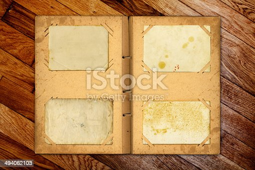 istock Open photoalbum with ribbon for photos on the wooden table 494062103