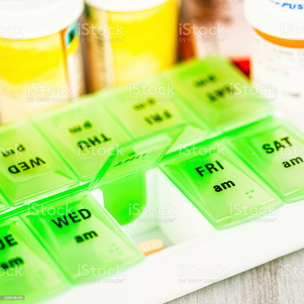 Open pill organizer with pills stock photo