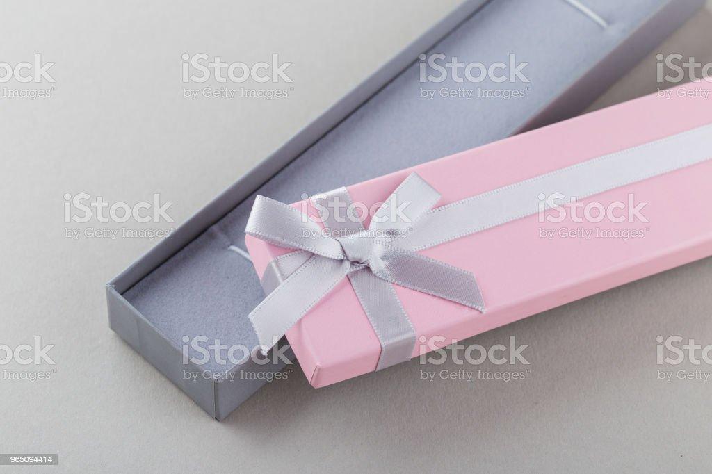 Open pink gift box with ribbon bow on gray background zbiór zdjęć royalty-free