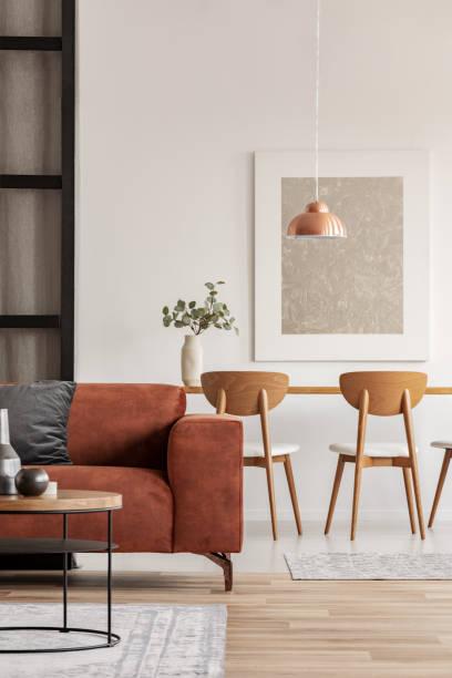 ouvert salon et salle à manger intérieur avec longue table avec chaise, canapé de velours brun - marron couleur photos et images de collection