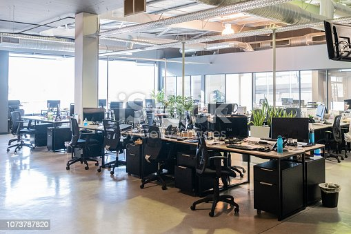 Modern office with desks and chairs, natural light coming though window, spacious work environment