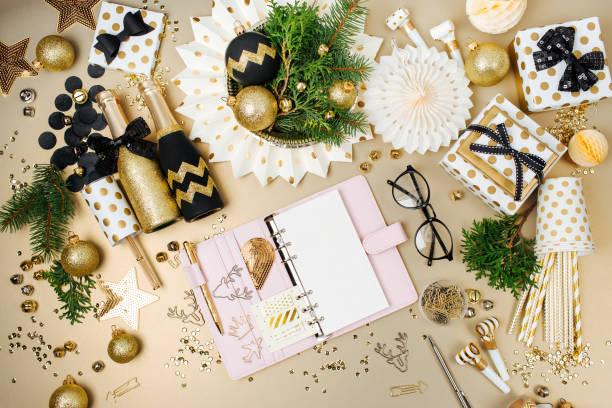 offenen planer oder notebook am schreibtisch mit weihnachten dekoration hintergrund in goldenen und schwarzen farben. flach legen, top aussicht - menüplanung vorlagen stock-fotos und bilder