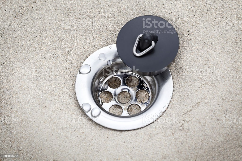 Open plughole in the sand stock photo