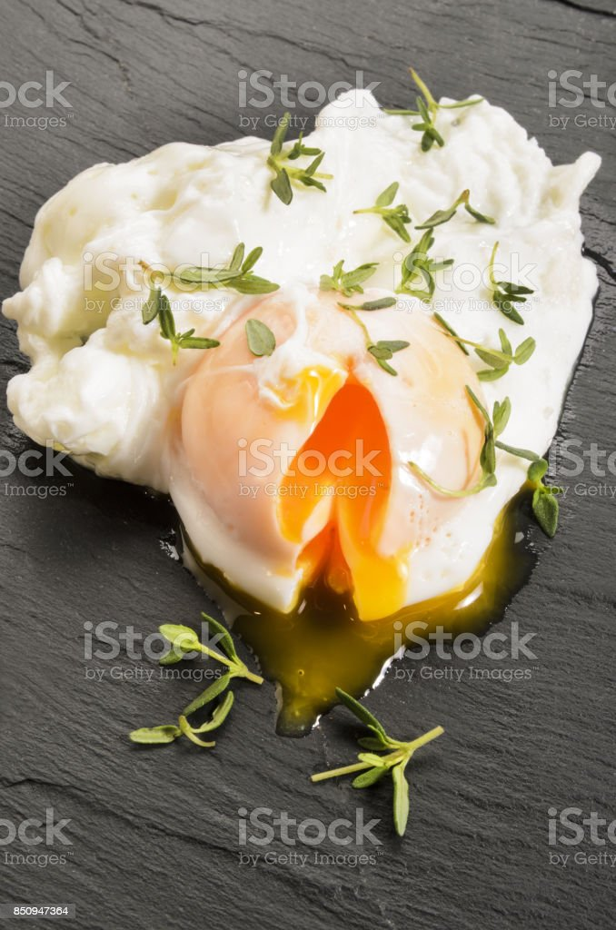 open poached egg with thyme on slate stock photo